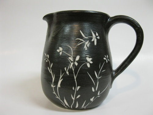 Etched flowers on a black glazed pitcher